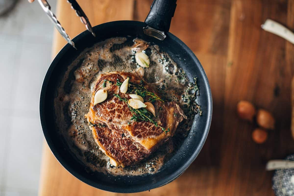 A ribeye steak, frying in a pan with rosemary, garlic and butter