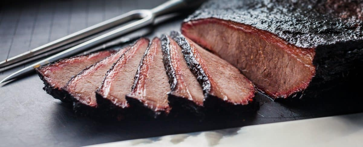 A sliced brisket flat with deep bark and light smoke ring