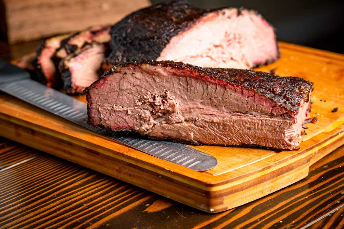 A brisket with smoke ring, cut in half, on a cutting board with a large knife