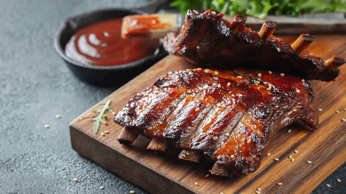 A rack of pork ribs on a cutting board, brushed with sauce