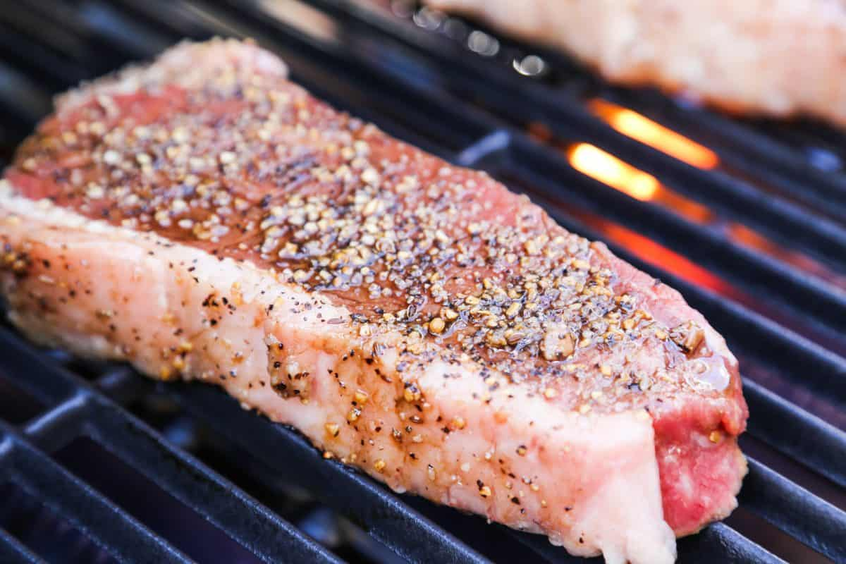 A thick sirloin steak sitting on a charcoal grill grate